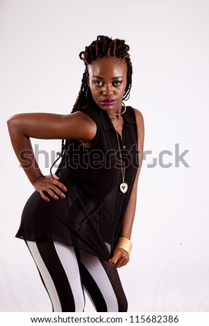 Cute black woman in black and white striped pants,  with her hand on her hip, looking into the camera with a serious expression - stock photo