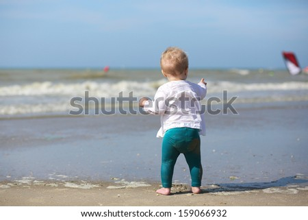 Cute blond baby girl in white blouse is standing next the water on the beach at a North Sea in Belgian coast on a sunny summer day looking at the yachts
