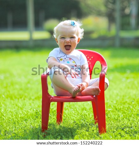 Cute blond baby girl laughing and enjoying the sun sitting on a small red chair in a garden - stock photo