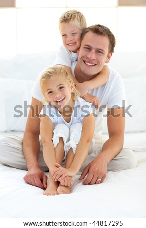 Cute blond boy hugging his dad sitting on a bed at home