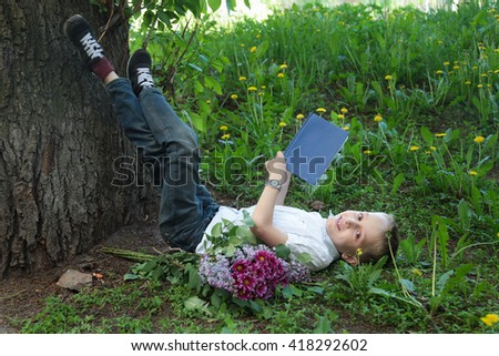 Cute blond boy in white shirt reads book near big tree beautiful spring day - stock photo