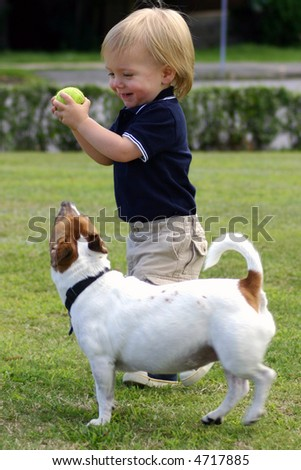 Cute blond Boy, one year old and his pet dog playing catch, fetch mischief - stock photo