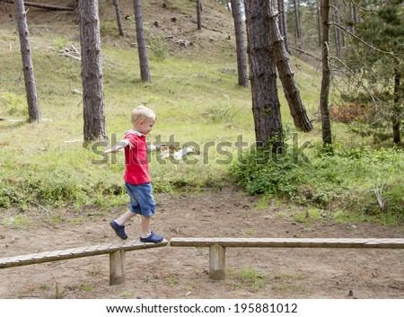 Cute blond boy walking along a wooden beam - stock photo