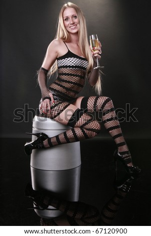 Cute blond enjoys a champagne flute while sitting on a silver ottoman - stock photo