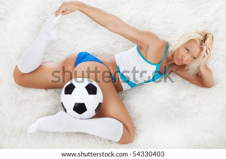 Cute blond fan lying with ball - stock photo