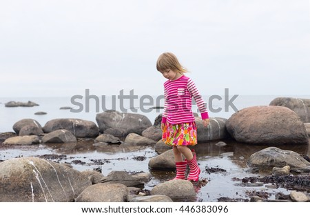 cute blond girl in preschool age wearing bright pink clothing and striped rainy boots playing in shallow sea water on rocky northern coast - stock photo