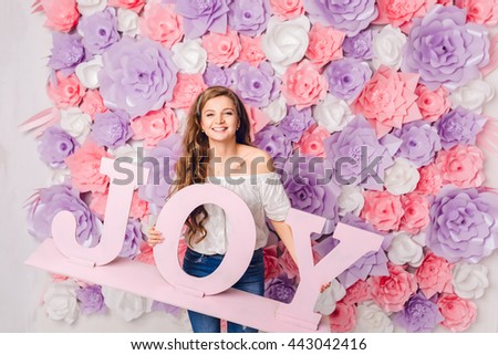Cute blond girl stands and holds wood word JOY smiling widely. She has long curly hair and wears blue jeans and white t-shirt off the shoulder.She has pink background covered in flowers. - stock photo