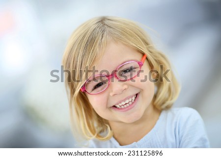 Cute blond little girl with pink eyeglasses - stock photo