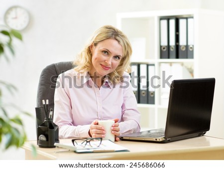 Cute blond mature businesswoman working on laptop and drinking coffee - stock photo