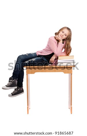 Cute blond schoolgirl sitting on her desk with a pile of books nearby - stock photo