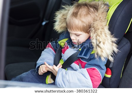 cute blond smiling boy five years old in the winter sitting in a car in a child car seat to 36 killogramm, buckled and is safe is not looking at the camera