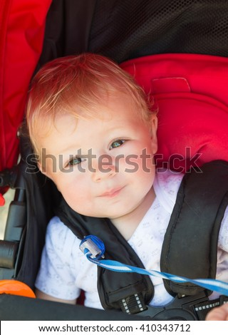Cute blond toddler baby sitting in a stroller at summer day