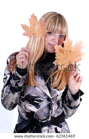 cute blond with yellow autumn leaf in the hands