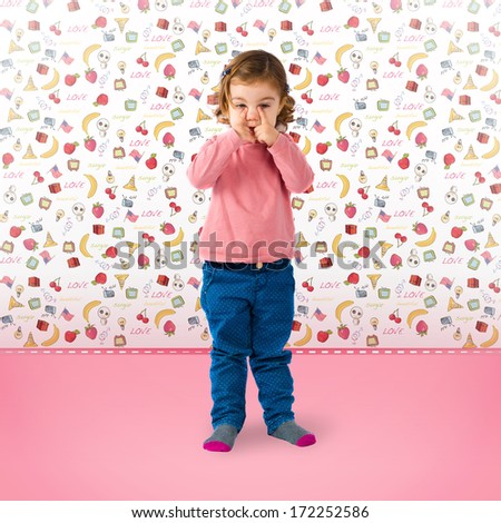 Cute blonde baby crying in a pink room - stock photo