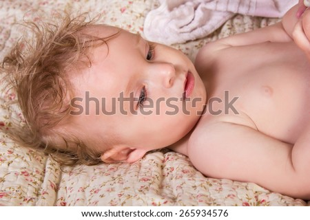 Cute blonde baby girl with beautiful blue eyes lying on bed  - stock photo