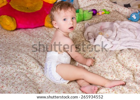 Cute blonde baby girl with beautiful blue eyes sits on bed in diapers with toy - stock photo