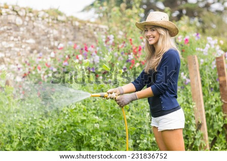 Cute blonde gardening on sunny day at home in the garden - stock photo