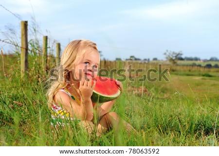 Cute blonde girl eats a watermelon in a field - stock photo