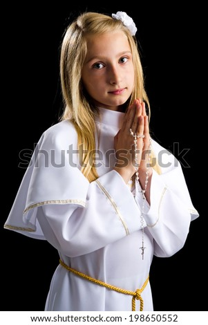 Cute blonde girl in first communion alb on black background - stock photo