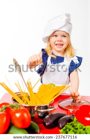 Cute blonde girl in white cap cook standing beside wooden table  - stock photo
