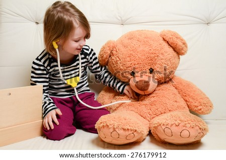 Cute, blonde girl playing doctor with plush toy bear