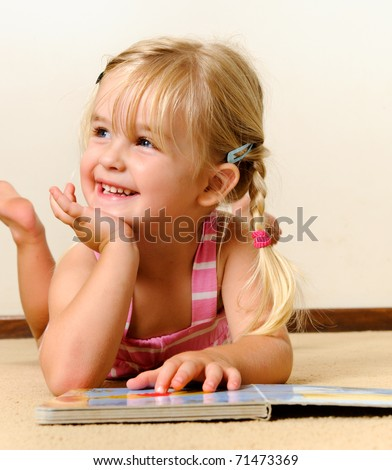 cute blonde girl with pigtails laughs and reads a book at kindergarten - stock photo