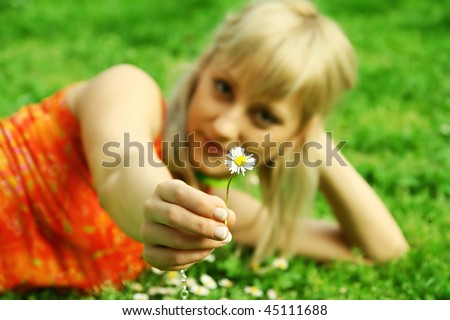 Cute blonde giving a daisy to the viewer ( focus on the daisy) - stock photo