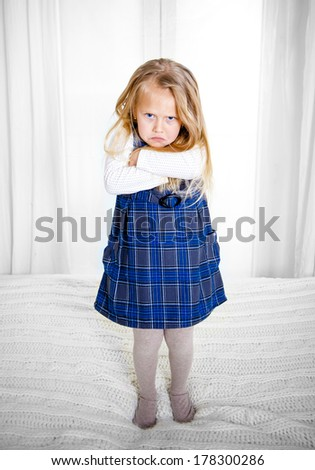 cute blonde haired girl wearing a blue dress frowning and looking angry at the camera standing on the bed - stock photo