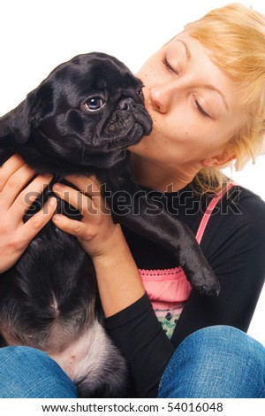 Cute blonde holding and kissing a pug - stock photo