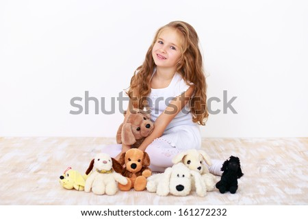 Cute blonde little girl in white dress sitting on the floor with her teddy dogs - stock photo