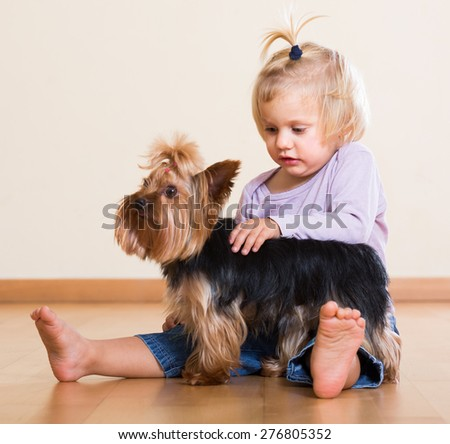 Cute blonde little girl playing with Yorkshire Terrier on the floor indoor - stock photo