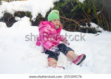 Cute blonde little girl sitting in the snow in her backyard in Jerusalem with tired expression - stock photo