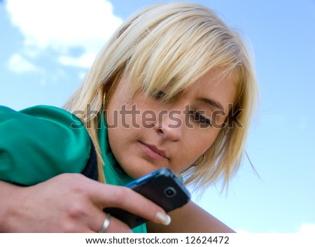 Cute blonde messaging on the blue sky background - stock photo