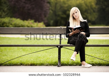 cute blonde sitting in the park reading book. Front view - stock photo