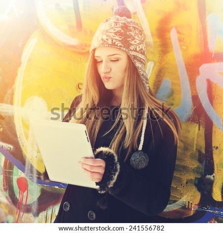 Cute blonde teenage girl with digital tablet and knitted modern hat outdoors against graffiti wall. Square format, instagram filter, sunlight. - stock photo