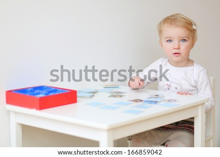 Cute blonde toddler girl playing memory game sitting at little white table indoors at home or kindergarten - stock photo