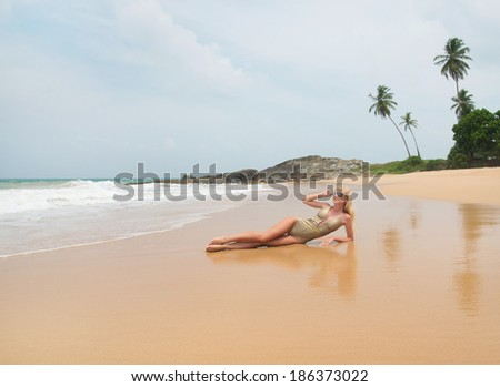 Cute blonde woman at ocean beach with palm trees - stock photo
