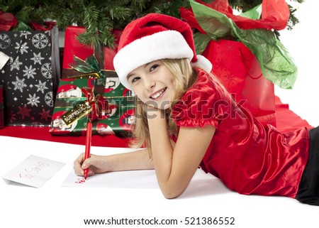 Cute blonde young girl with santa hat writing a christmas list by the tree isolated on white background
