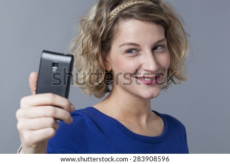 Cute blonde young woman smiling for selfie portrait on mobile phone