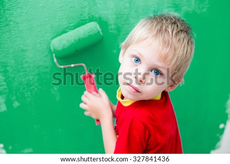 Cute blue-eyed blond pretty boy of five years in the red t-shirt makes repair paints the wall in blue roller