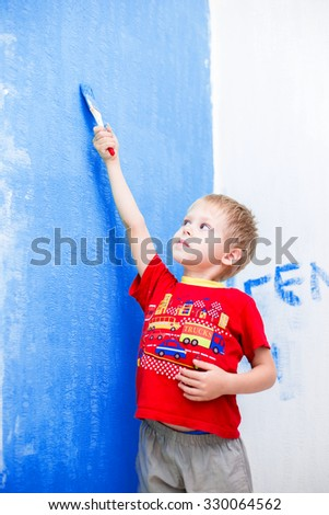 Cute blue-eyed blond pretty boy of five years in the red t-shirt makes repair paints the wall in blue paint brush - stock photo