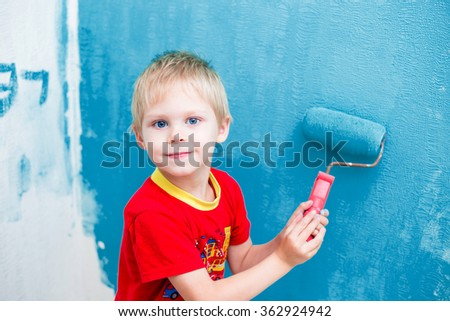 Cute blue-eyed blond pretty boy of five years in the red t-shirt makes repair paints the wall in blue roller - stock photo