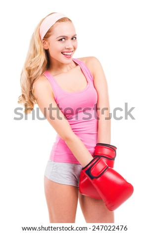 Cute boxer. Beautiful blond hair woman in pink shirt and boxing gloves looking at camera and smiling while standing isolated on white background - stock photo