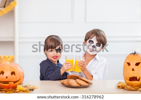Cute boy and girl are making fun in Halloween. They are sitting in kitchen and drinking juice. The friends have spooky make-up on their faces and smiling. There are pumpkins and cookies on the table - stock photo