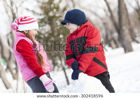 Cute boy and girl building snowman in winter park - stock photo