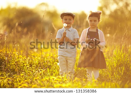 cute boy and girl on summer field - stock photo