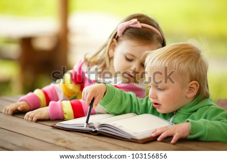 cute boy and girl reading a book - stock photo