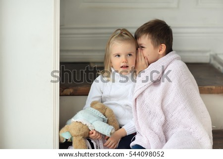 cute boy and girl 4 years old dressed in a white sweater and jeans sitting on white stairs at home with a toy rabbit wrapped in pink blanket and tell secrets