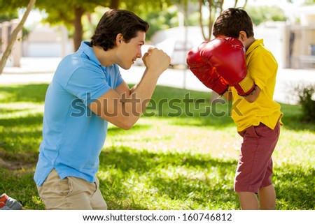 Cute boy and his dad wearing boxing gloves and having fun outdoors - stock photo