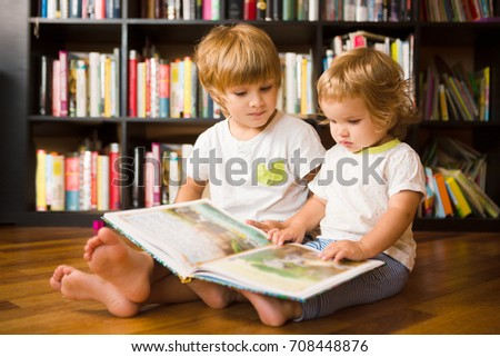Cute boy and his little sister  reading a book together  near bookshelf at home